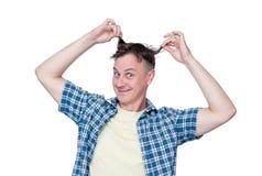 El hombre feliz divertido en una camisa de tela escocesa se sostiene el pelo, aislado en el fondo blanco foto de archivo libre de regalías