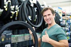 El hombre feliz elige el neumático para bike en tienda de los deportes Imagenes de archivo