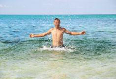 El hombre feliz en el mar con salpica Foto de archivo libre de regalías
