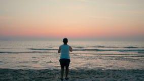 El hombre feliz está corriendo rápidamente y está saltando arriba en la costa de mar en la playa en la puesta del sol metrajes
