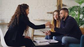 El hombre feliz está hablando con el agente inmobiliario, acuerdo de firma y está consiguiendo la llave de la casa, sacudiendo la