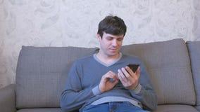 El hombre feliz está mecanografiando un mensaje en el teléfono que se sienta en el sofá Charla con el amigo almacen de metraje de vídeo