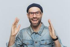 El hombre feliz hermoso aumenta las manos con el entusiasmo, tiene ex extático foto de archivo
