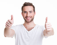 El hombre feliz joven con los pulgares para arriba firma adentro casual. Imagen de archivo libre de regalías