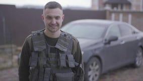 El hombre feliz joven en militares se cierra en la situación del chaleco a prueba de balas delante del coche en la yarda en casa, almacen de video
