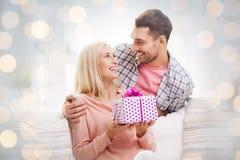 El hombre feliz que da a la mujer presente durante día de fiesta se enciende Imagen de archivo libre de regalías