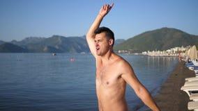 El hombre feliz que engaña alrededor en la playa, baila y salta cerca del mar contra un fondo de montañas y del cielo azul almacen de video
