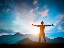 El hombre feliz que mira las montañas maravillosas ajardina en la puesta del sol Fotos de archivo libres de regalías