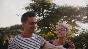 El hombre feliz relajado y la mujer de la cámara lenta caminan juntos abrazándose y hablando en un parque hermoso de la puesta de metrajes