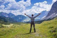 El hombre feliz se está colocando en una colina Imágenes de archivo libres de regalías