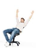 El hombre feliz se incorpora en la silla y las manos aumentadas Foto de archivo