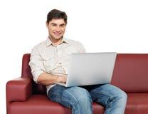El hombre feliz sonriente con la computadora portátil se sienta en el diván fotografía de archivo libre de regalías