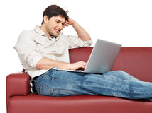 El hombre feliz sonriente con la computadora portátil se sienta en el diván imagen de archivo