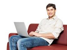 El hombre feliz sonriente con la computadora portátil se sienta en el diván foto de archivo