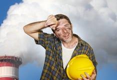 El hombre feliz y cansado atractivo del trabajador del contratista o de construcción que llevaba a cabo el casco de seguridad y l fotografía de archivo libre de regalías