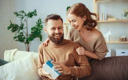 El hombre feliz y la mujer de la pareja de matrimonios dan un regalo para el d?a de fiesta imagenes de archivo