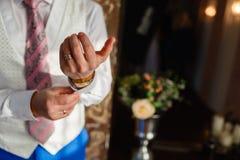 El hombre fija los puños en la camisa blanca y los pantalones elegantes del chaleco y azules con los accesorios, los relojes, los Imágenes de archivo libres de regalías