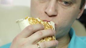 El hombre flaco come el bocado de los alimentos de preparación rápida con el gran disfrute individuo que mastica la comida basura almacen de metraje de vídeo
