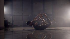 El hombre flexible se coloca en sus manos en un gimnasio almacen de video