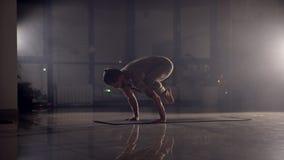 El hombre flexible se coloca en sus manos en un gimnasio almacen de metraje de vídeo