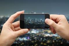 El hombre fotografía la ciudad de la noche Imágenes de archivo libres de regalías