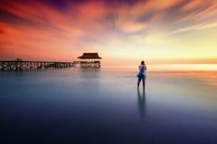El hombre fotografió puesta del sol cerca del embarcadero Imagenes de archivo