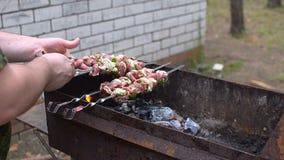 El hombre fríe el kebab en los pinchos, una barbacoa