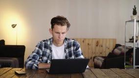 El hombre frustrado enojado rompe el ordenador portátil en la tabla almacen de video