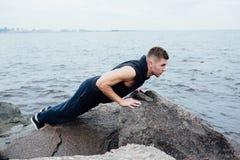 El hombre fuerte actúa yoga en las rocas vara por la mañana contra el mar Fotos de archivo