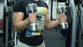 El hombre fuerte atlético levanta pesas de gimnasia en un gimnasio brillante almacen de metraje de vídeo