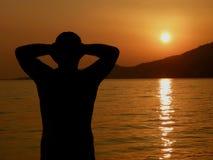 El hombre fuerte, atractivo se relaja en puesta del sol en el mar Fotografía de archivo