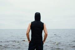 El hombre fuerte de la aptitud de yang presenta en la playa cerca del mar y de rocas Imagenes de archivo