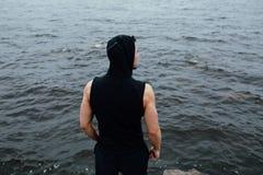 El hombre fuerte de la aptitud de yang presenta en la playa cerca del mar y de rocas Imagen de archivo