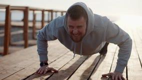 El hombre fuerte está haciendo flexiones de brazos al aire libre por mañana soleada almacen de metraje de vídeo