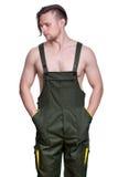 El hombre fuerte joven con un torso desnudo en un uniforme de trabajo pegó h Fotos de archivo libres de regalías