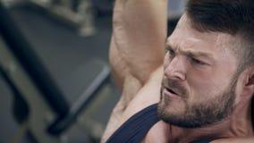 El hombre fuerte levanta los pesos pesados de arriba en gimnasio almacen de video