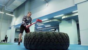 El hombre fuerte muscular con un martillo golpea la rueda enorme adentro el gimnasio en la cámara lenta metrajes