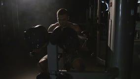 El hombre fuerte, muscular enganchó a los deportes, aptitud en el simulador almacen de video