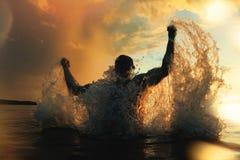 El hombre fuerte y atlético salta del agua en la puesta del sol Foto de archivo libre de regalías