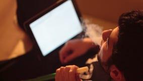 El hombre fuma una cachimba y una tableta de las aplicaciones Fotos de archivo libres de regalías
