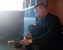 El hombre fuma y marca SMS imagen de archivo