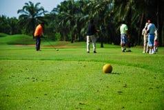 El hombre golpeó golf en hierba verde del agujero Foto de archivo