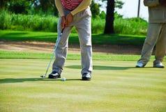El hombre golpeó golf en hierba verde del agujero Imagen de archivo libre de regalías