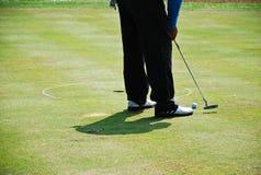 El hombre golpeó golf en hierba verde del agujero Imágenes de archivo libres de regalías
