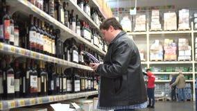El hombre gordo atractivo joven está eligiendo la buena botella de vino en el supermercado almacen de video