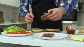 El hombre gordo cocina las hamburguesas en casa El individuo regordete pone una chuleta en un bollo Caloría malsana de la forma d metrajes