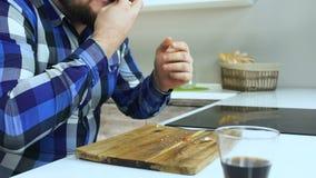 El hombre gordo come encima de la hamburguesa que él hizo El individuo limpia su boca con una servilleta El varón sale Forma de v almacen de metraje de vídeo