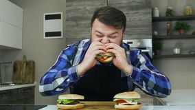 El hombre gordo come y goza de su hamburguesa La persona con una barba come la comida que él cocinó Forma de vida malsana, frita  almacen de metraje de vídeo