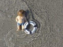El hombre gordo con el anillo de la natación miente en la playa Foto de archivo libre de regalías