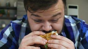 El hombre gordo con una barba muerde un pedazo de hamburguesa La comida es muy deliciosa El individuo regordete está alegre Forma metrajes